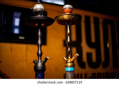 Hookah bar. Background is blurred. In the foreground there are two large hookahs. Two Arabic Shishi tubes, against a light brown wooden wall