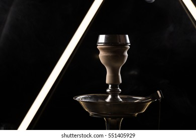 Hookah bowl with tobacco and smoke on black background