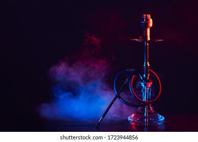 hookah with a glass flask and a metal bowl shisha with colored smoke on the table on a black background with a copy space