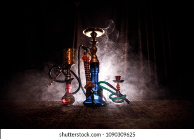 Hookah hot coals on shisha bowl making clouds of steam at Arabian interior. Oriental ornament on the carpet. Stylish oriental shisha in dark with backlight. For Shisha advertisement. Selective focus