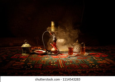 Hookah hot coals on shisha bowl making clouds of steam at Arabian interior. Oriental ornament on the carpet eastern tea ceremony. Stylish oriental shisha in dark with backlight. Selective focus