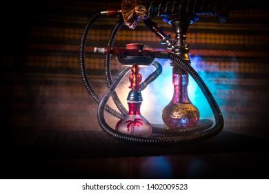 Hookah hot coals on shisha bowl on dark foggy background. Stylish oriental shisha. Creative concept