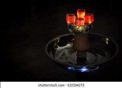 Hookah hot coals on shisha bowl with black background.