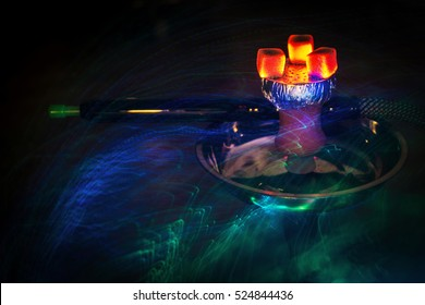 Hookah hot coals on shisha bowl with mouthpieces and color lights