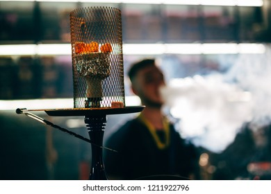 Hookah with hot coals with smoker on the background of a man