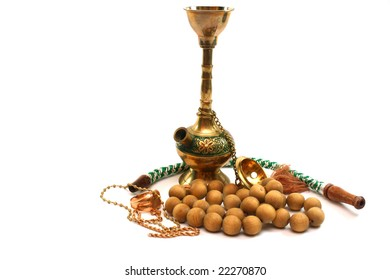 hookah iron, gold jewelry and wooden beads on a white