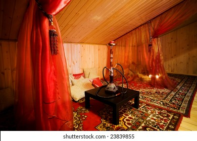Hookah on a black table in a beautiful wooden room