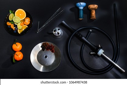 Hookah parts smoking hookah concept at black background isolated with fresh fruits and ice. Hookah bowl, coil, forceps, silicone hose, mounthpiece and kaloud