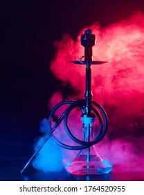 hookah shisha with glass flask and metal bowl with colored smoke on a black background. Traditional Eastern vacation for relaxation