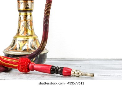 hookah or shisha is standing on a wooden table with a white background