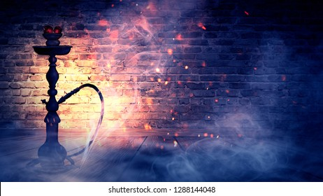 Hookah, smoke, burning coals, old brick wall and neon light. Night view, sparks and lights.