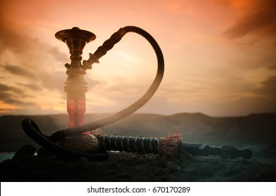 Hookah, traditional arabic waterpipe, direct sunset light, outdoor photo. Mountain background