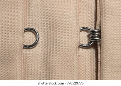 Hook-and-eye closure on clothes of beige color macro