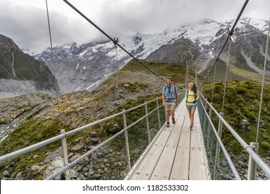 Hooker Valley Track hiking trail, New Zealand. Hikers people crossing bridge on the Hooker Valley track, Aoraki, Mt Cook National Park with snow capped mountains landscape.