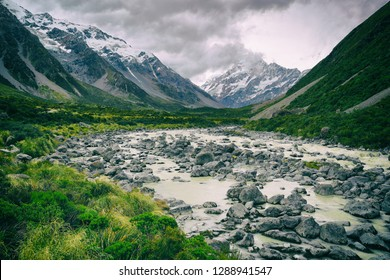 Hooker Valley Track hiking trail, New Zealand. River leading to Hooker lake with glacier over view of Aoraki Mount Cook National Park with snow capped mountains landscape. Summer nature.