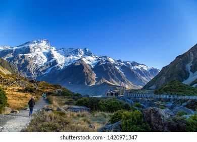 Hooker valley track local path with woman and other tourist trekking to a bridge against snow covered Sefton mountain and blue sky