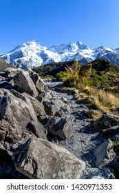 Hooker valley track with rock climbing walking path against snow covered Sefton mountain and blue sky , Aroki/Mtcook National park, New Zealand