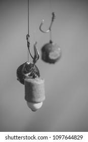 Hooks with fishing bait, chumming. Fishing, angling, catching fish, chum. Fishhooks on line on blurred background