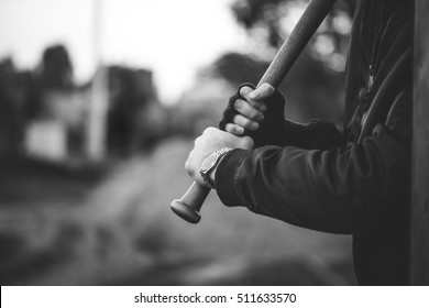 hooligan with the baseball bat in hands ready to attack from hiding
