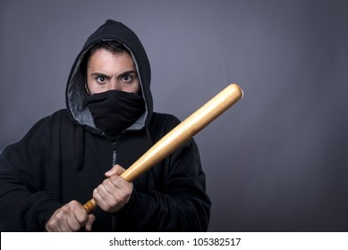 Hooligan with baseball bat ready for fight - copy space