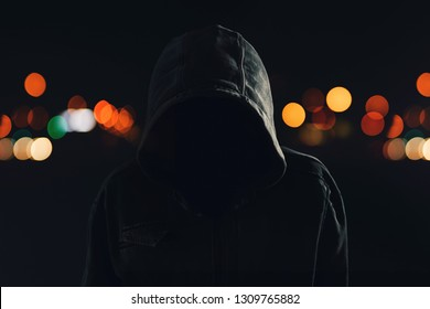 Hooligan with hoodie and obscured face walking the city streets at night, looking spooky and threatening