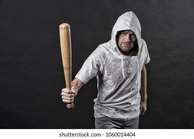 Hooligan wear hood in hoody, fashion. Man hold baseball bat, aggression. Gangster guy threaten with bat weapon. Aggression, anger and violence concept, vintage