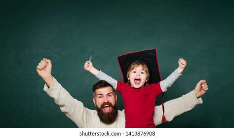 Hooray. Concept of education and teaching. Elementary school teacher and student in classroom. Age and Ageing. Man teaches child. Blackboard for copy space text. Triumphing from great news
