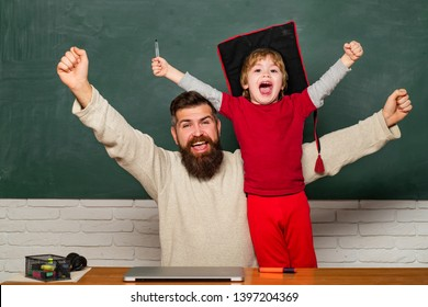 Hooray. Daddy and son raising clenched fists in hooray gesture. Father teaching her son in classroom at school. Yeah good work. Happy father and son over chalkboard. Daddy and son together