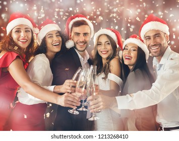 Hooray. Diverse friends clinking with champagne flutes, celebrating together on New Year's Eve party