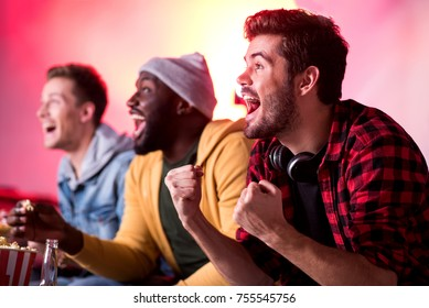 Hooray. Happy young friends are screaming and expressing gladness while sitting on couch and watching match at home. Focus on pleasant stylish man with headphones on his neck