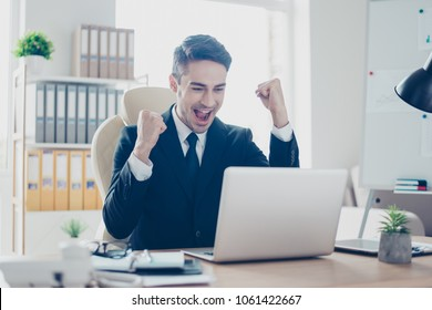 Hooray! Portrait of cheerful delightful handsome with open mouth screaming satisfied amazed astonished freelancer looking at computer's monitor raising hands up sitting at the table