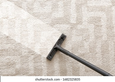 Hoovering of carpet with vacuum cleaner, top view