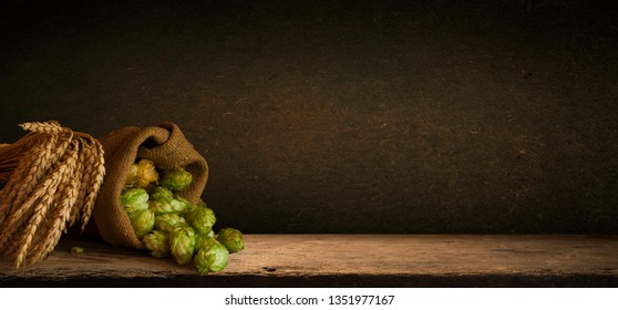 Hop twigs frame over wooden cracked table background. Vintage toned. Beer ingredients. Beautiful fresh-picked whole hops with green leaves border design close-up. Brewing concept, Vertical image
