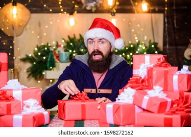 Hope for the best. Wrapped gifts with ribbons and bows. Man bearded santa claus hat celebrate new year. Hipster prepared gifts for family. Generous new year. Lot of gifts. Happy winter holidays.