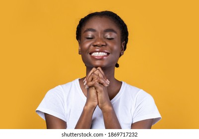 Hope Concept. Black Young Woman Praying God Holding Hands In Prayer Gesture Smiling With Eyes Closed Over Yellow Background. African Lady Prays Posing In Studio.