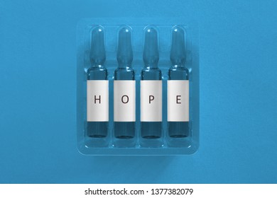 Hope for cure and treatment concept image. Four ampules with overlay letters of inscription H O P E