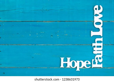 Hope, Faith and Love hanging on rustic teal blue wood sign; spiritual holiday background with copy space