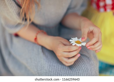 hope, girl guessing on chamomile / baby with chamomile flower, concept divination hope love love friendship