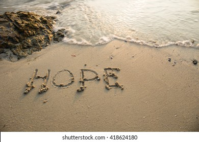 Hope written in the sand at the beach waves in the background.