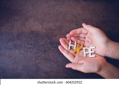 Hope with yellow gold ribbons on hands, Sarcoma Awareness, Bone cancer, Liver cancer, Bladder Cancer, childhood cancer awareness, World Suicide Prevention Day, September yellow