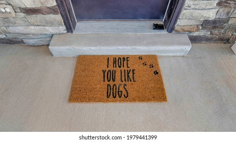 I hope you like dogs doormat at the doorstep of home with gray front door. Top view of the entrance of house with stone exterior wall.