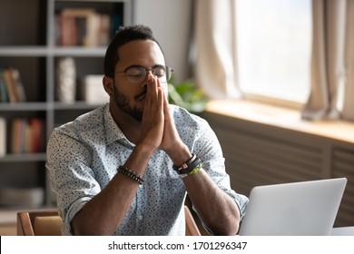 Hoffnungsvoller afroamerikanischer Gläubiger sitzt am Schreibtisch und betet Gott um Glück bitten, nachdenklicher birazial-abergläubischer Mann hält Hände in Gebet fühlen dankbar, Glaube, Religion Konzept