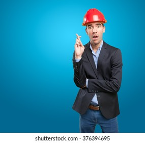 Hopeful architect with crossed fingers gesture