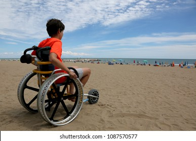 hopeful boy looks at the sea from the wheelchair at the beach