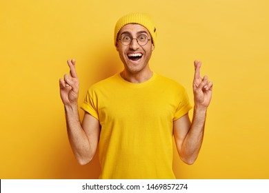 Hopeful cheerful guy crosses fingers for good luck, dreams about something or expects miracle, anticipates good news, wears yellow hat and t shirt makes wish or aims success hopes for excellent result