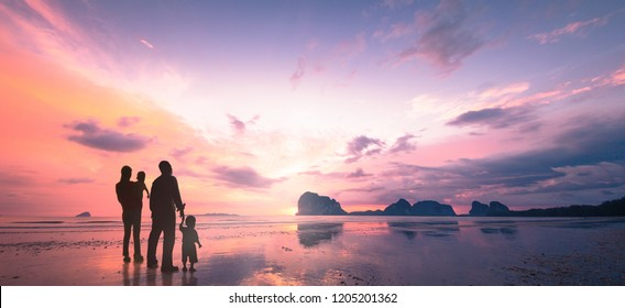 Hopeful concept: Father, mother and two son over water on beach sunrise background