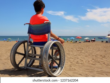 hopeful disabled boy in a wheelchair looks at the blue sea