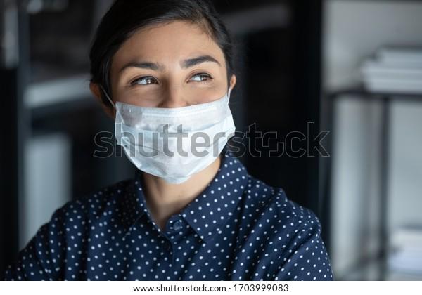 Joven esperanzada sonriente con mascarilla protectora mira a distancia esperanza por el final de la pandemia del coronavirus, feliz milenario mujer con cubierta facial médica del pensamiento COVID-19, concepto de salud
