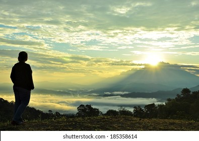 The hopeful Sunrise. Silhouette of a person looking at the sunrises from behind the mountain.