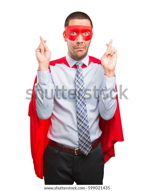 Hopeful super businessman finger cross gesture